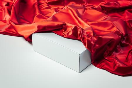 Gros plan d'une boîte vierge blanche sous un tissu rouge sur fond blanc. rendu 3D.