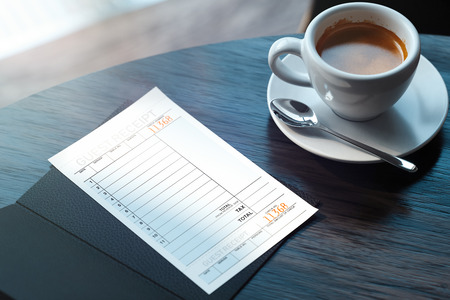 Close up of cheque and coffee cup on wooden table in modern cafe. 3d rendering.
