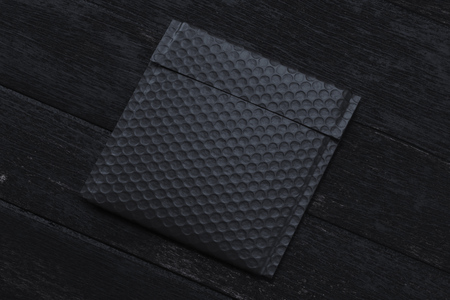 Black realistic packet isolated on black background. 3d rendering. Top view. copy space. Empty space.