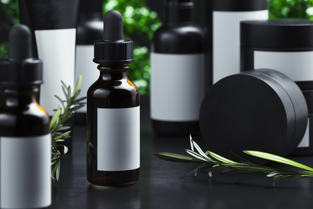 Cosmetic Bottle with olive oil, cream, gel or lotion. Beauty product package, blank template of glass container in black cardboard packages next to Olive tree branch on dark background. 3d rendering.