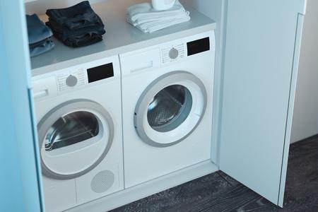 Realistische weiße Wasch- und Trocknermaschinen mit Waschmittel und Kleidung oben in modernem, hellem Interieur. 3D-Rendering. Ansicht von oben. Standard-Bild