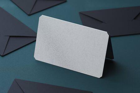White blank business card and black envelopes on dark background. 3d rendering.