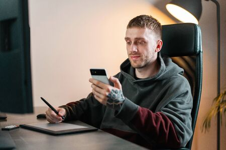 Young attractive man working on Graphics tablet. Modern working place of designer, painter, photographer.