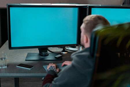 Man working on PC with blank monitors. Modern working place of designer, painter, photographer, freelancer. 스톡 콘텐츠
