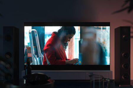 Gran televisor negro con película filmada en un armario blanco en un interior moderno, renderizado 3d. Vista frontal. Foto de archivo
