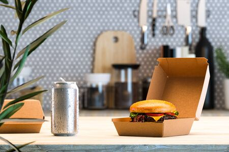 Fresh Cheeseburger in Blank Box From Recyclable Craft Paper Or Cardboard Near Aluminium Can With Cold Water Droplets In Modern Stylish Kitchen Interior. Delivery. Copy space. Empty Space. 3d rendering Reklamní fotografie