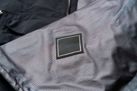 Blank Black Square Clothing Label Mockup Template on Stylish Black Sportswear. Tag Label With Copy Space, Empty Space. Reklamní fotografie