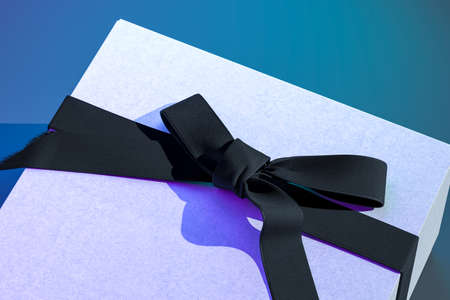 Close up of blank gift box with bow for greetings concept. Present package template. White gift box with black ribbon bow on blue background. 3d rendering. High quality 3d rendering.