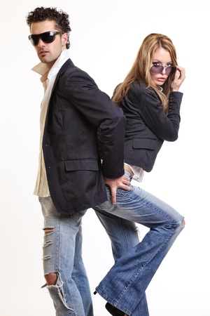 women in jeans: fashion couple posing in studio