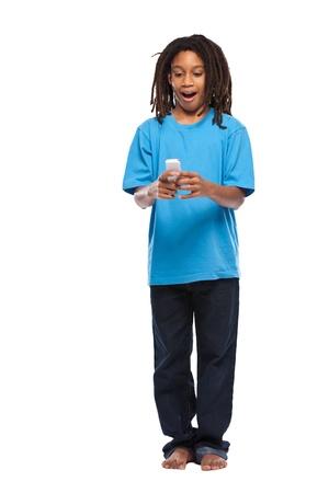piedi nudi ragazzo: giovane ragazzo africano in posa con cellulare in studio Archivio Fotografico