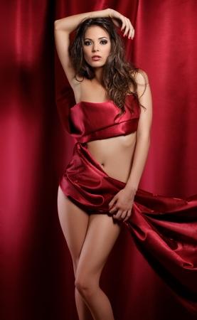 mujer envuelta en rojo textil Foto de archivo