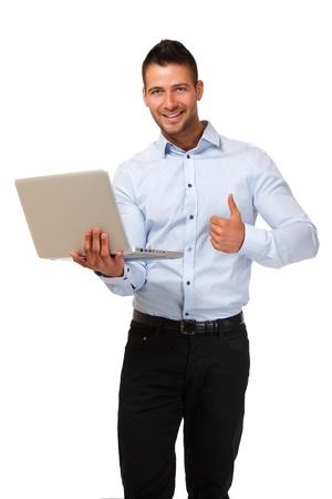 young man standing: giovane uomo in piedi in studio con il computer portatile Archivio Fotografico