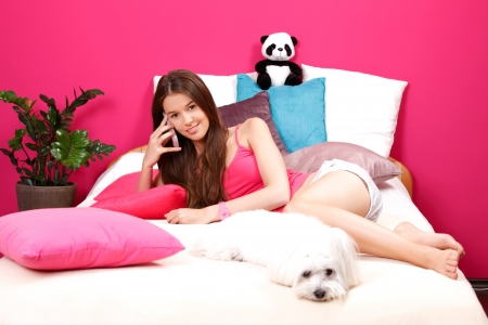 ly: nice young woman speaking on cellphone with her girlfriend and lying with her white dog