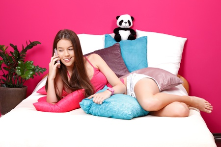 natural young woman making a call in her pink room photo