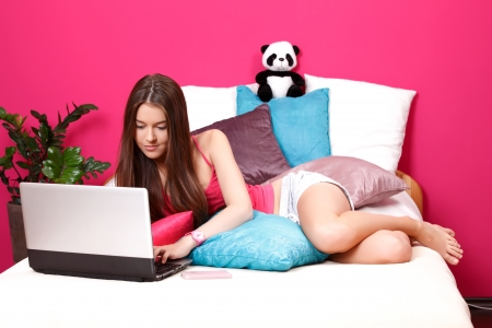 nice young woman typing on her laptop photo