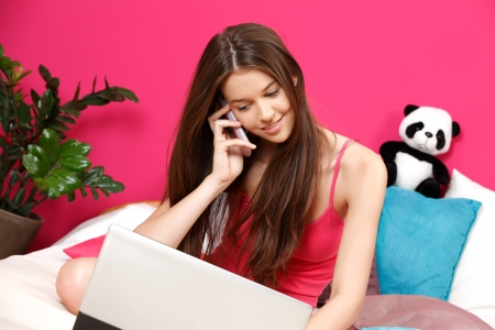 teenager girl using her laptop and making a phonecall photo