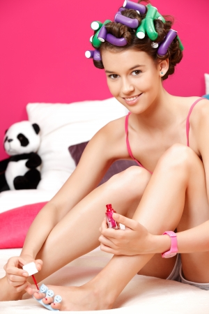 happy young woman painting her toenails in her room photo