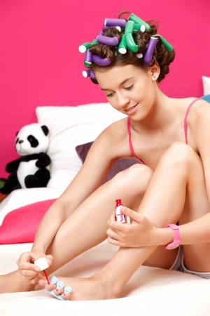 nice young woman painting her toenails photo