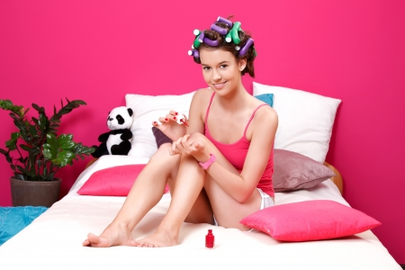 nice young woman preparing herself in her pink room photo