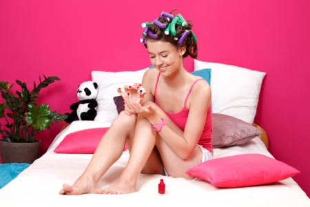hair dye: young manicurist applying red nail polish on her nails