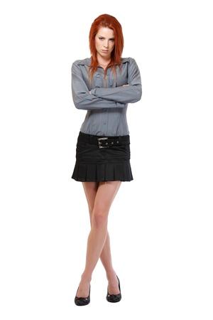 cross leg: mujer pelirroja posando en el estudio serio