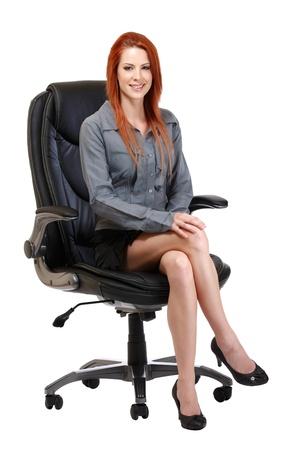 cross leg: mujer bonita con el pelo rojo aislado en blanco