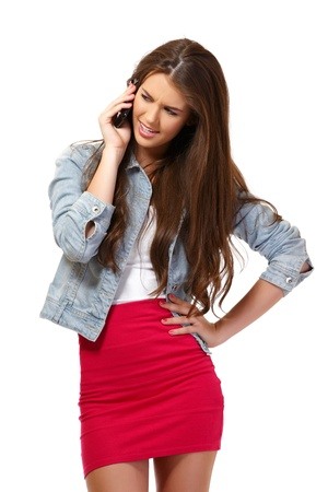 angry young woman with cellphone in studio Stock Photo - 14724282