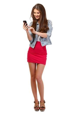 falda corta: mujer joven bonita posando con el teléfono en el estudio