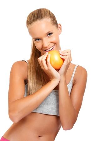 sportry mujer con naranja aislado en blanco Foto de archivo