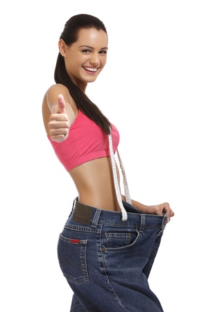 young brunette lady posing with big blue jeans isolated on white