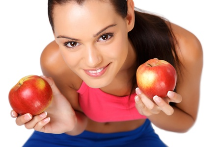 sporty: happy young woman sitting on the floor with apples isolated on white