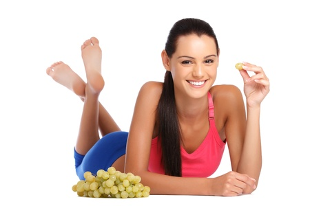 barefoot teens: beautiful young brunette teenager posing with grape on white background Stock Photo