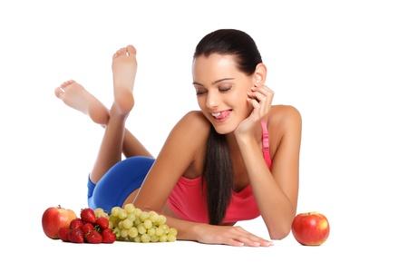 cross leg: mujer bonita joven tumbado en el suelo con frutos sanos
