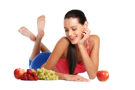 nice young woman lying on the floor with healthy fruits