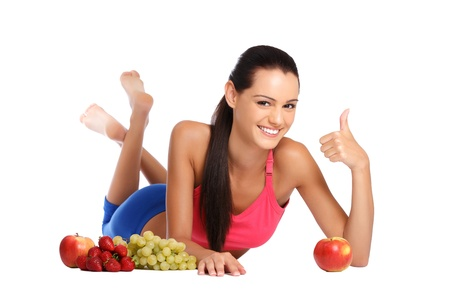 young brunette teenager posing with apples, strawberries, grapes on white background photo