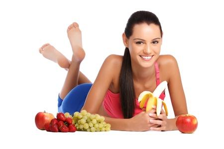 mujer bonita joven tumbado en el suelo con frutos sanos