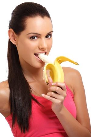brunette Teenager beißende Banane auf weißem Hintergrund Standard-Bild