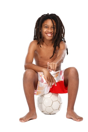 handsome young rasta man sitting on football on white background photo