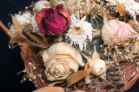 Bouquet of withered flowers in a wicker basket