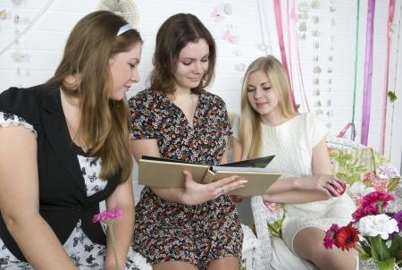 Girls consider the photo album Stock Photo - 18542423