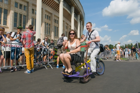 original bike: SIA, MOSCOW-JULY 13: Everyone wishing is given the opportunity to ride on makeshift unusual bikes on the Sports festival Moscow City Games 2013 in Moscow, Arena Luzhniki» on July 13, 2013. Demonstration unidentified cyclists riding