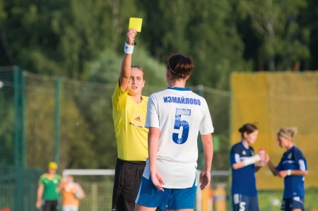 MOSCOW - AUGUST 18: Referee shows a yellow card football players in game Kubanochka vs CSP Izmailovo on Russian tournament of wemen football league on August 18, 2013, in Moscow, Russia
