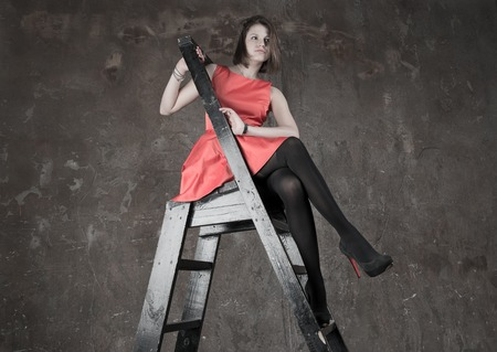 Studio portrait of confident beautiful slim woman model with awesome long legs wearing a red dress, shoes with high heels, sitting on steps of staircase, looking at camera photo