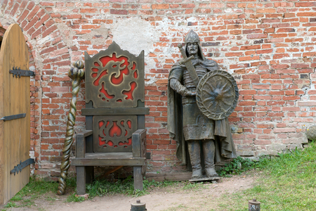 squad: VELIKY NOVGOROD, RUSSIA - AUGUST 08, 2015. Metal figure of ancient druzhinnik (member af ancient Slavic princes squad) next to the Prince throne at the Kremlin wall Editorial