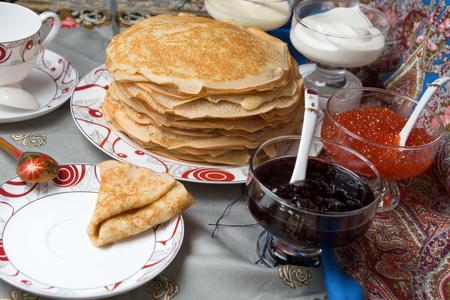 maslenitsa: Pancakes with red caviar, jam, cream and tea during Shrovetide