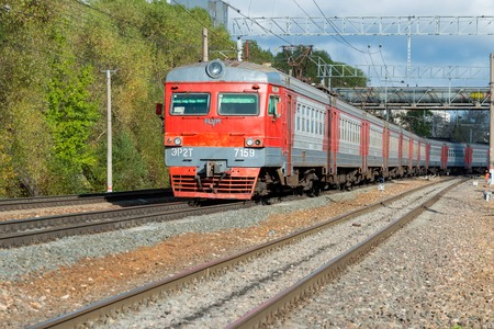 intercity: MOSCOW, RUSSIA - SEPTEMBER 30, 2015: Red train intercity from Dubna follows the railroad tracks in the city of Moscow