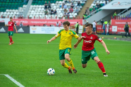 uniform green shoe: MOSCOW - MAY 11, 2016: Quarterback Georgy Zotov (15) in action during the soccer game Russian Premier League Lokomotiv (Moscow) vs Kuban (Krasnodar), the stadium Lokomotiv Moscow, Russia. Lokomotiv lost 0: 1