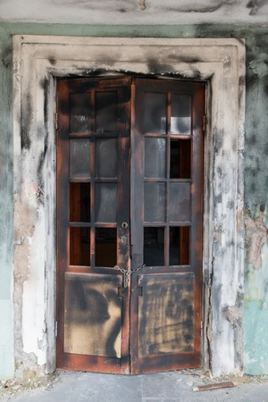 scorched: Scorched broken door of abandoned house