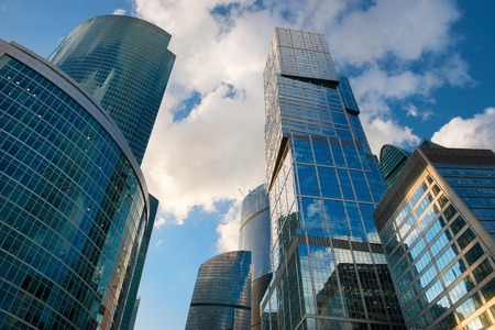 Steel and glass corporate buildings reflect the sky and clouds, Moscow