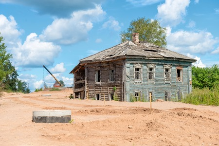 Old decaying evicted two-storey house at the construction site of the road Stock Photo